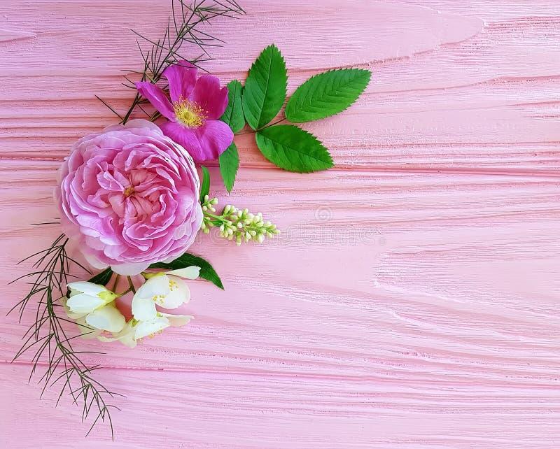 Blumenstrauß-Jahreszeitrahmen der Rosen schöner auf einem rosa hölzernen Hintergrundjasmin, Magnolie stockbild