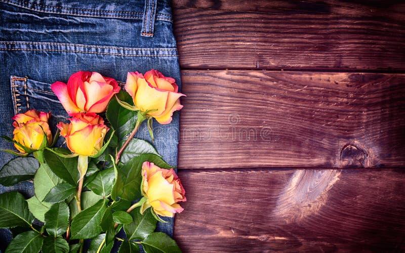 Blumenstrauß von blühenden Rosen auf Blau keucht Jeans lizenzfreies stockbild