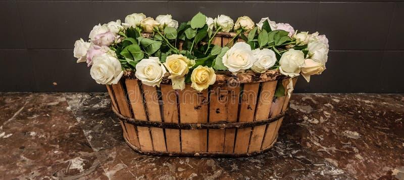 Blumenstrauß von blassen farbigen Rosen in einem hölzernen Korb Weicher Fokus Romantischer Hintergrund mit Kopienraum stockbilder