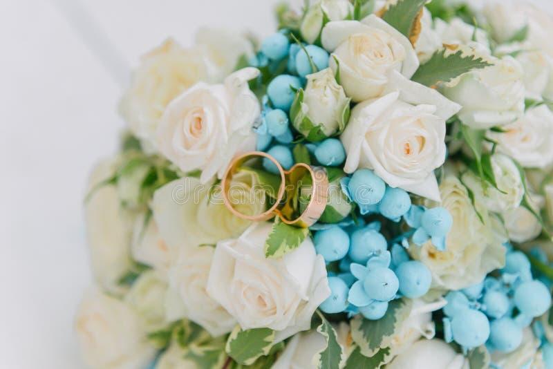 Blumenstrauß von Blumen Das bride& x27; s-Blumenstrauß Hände der Braut und des Bräutigams Floristics Heller weißer Hintergrund stockfotografie
