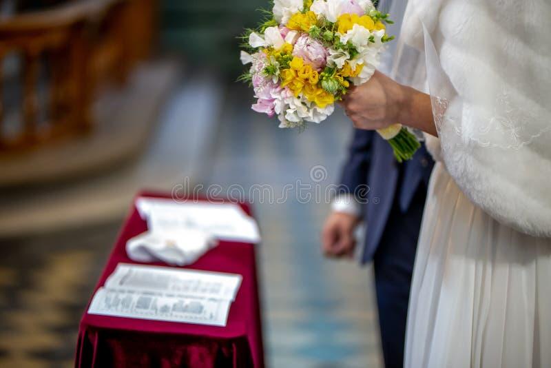 Blumenstrauß von Blumen in der Hand der Braut während der Trauung stockfotos