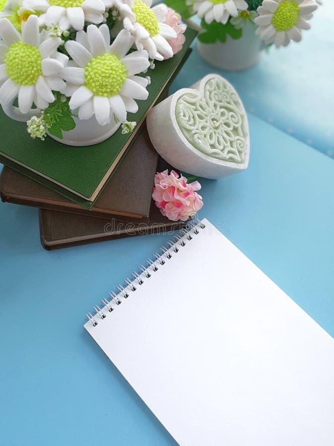 Blumenstrauß von Blumen in einem Vase, Bücher, dekoratives Herz, leerer Notizblock auf blauem Hintergrund stockfotografie