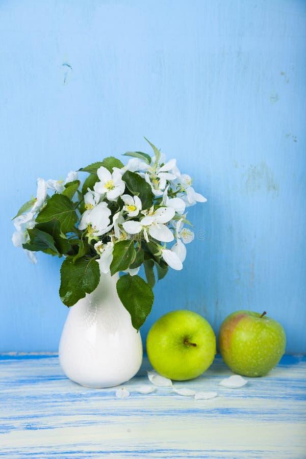 Blumenstrauß von Blumen in einem Vase und in grünen Äpfeln stockbilder