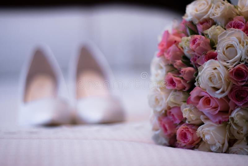 Blumenstrauß von Blumen und von Brautschuhen lizenzfreie stockfotos