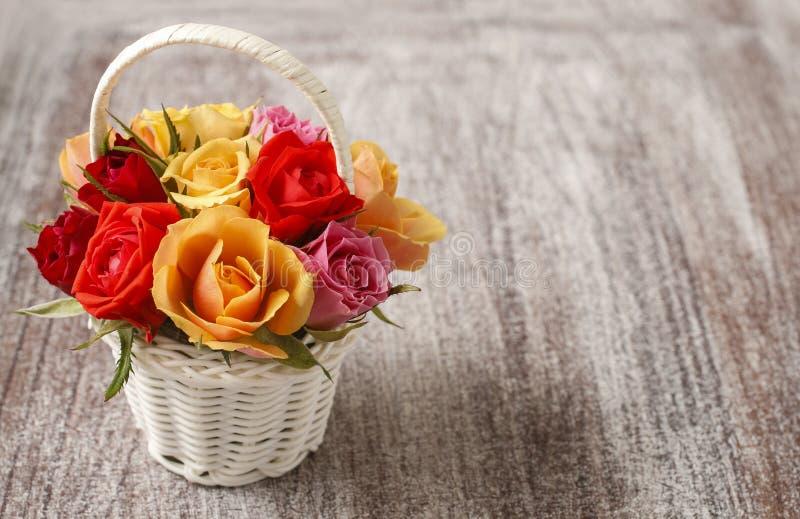 Blumenstrauß von bunten Rosen in einem weißen Weidenkorb lizenzfreies stockfoto