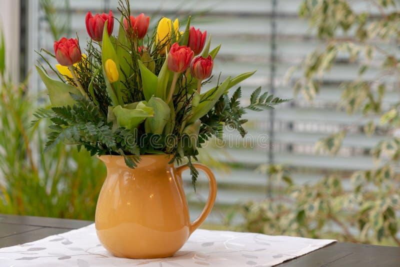 Blumenstrauß von bunten Tulpen steht in einem gelben Vase lizenzfreie stockfotos