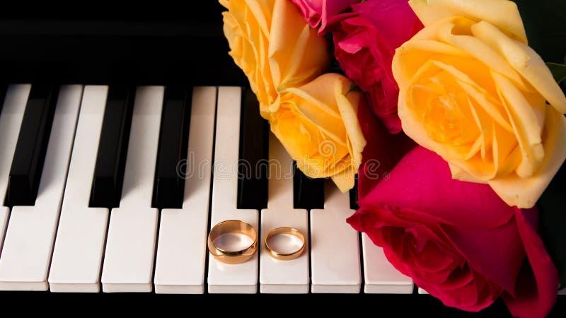 Blumenstrauß von den Rosen, die auf dem Klavier mit Eheringen liegen Hochzeitsgeschenk der gelben und roten Rosen mit Eheringen V stockfotografie