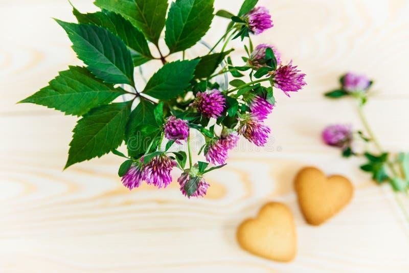 Blumenstrauß von der Blume, Herz formte Plätzchen auf Holztisch backgro lizenzfreies stockbild