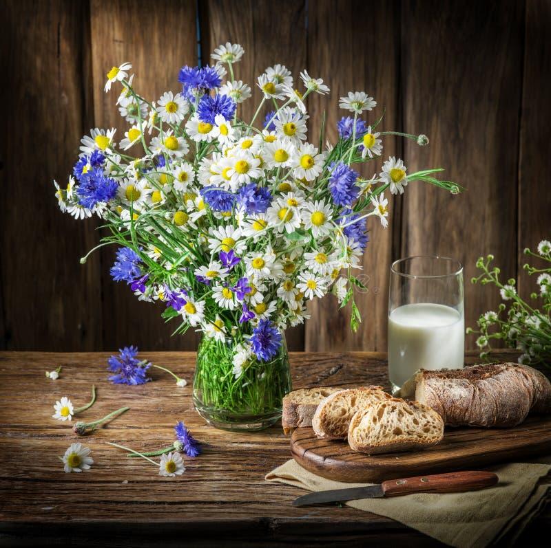 Blumenstrauß von Feldblumen, von Glas Milch und von weichem Brot lizenzfreie stockfotografie