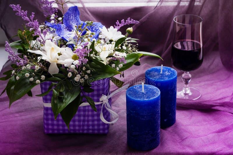 Blumenstrauß von Frühlingsblumen und von blauen Kerzen mit einem Glas Rotwein auf einem violetten Hintergrund, freier Raum für Te stockfotos