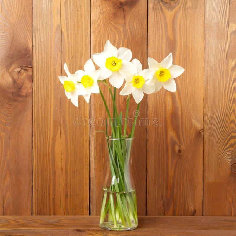 Blumenstrauß von frischen Blumen, Narzissen im Vase in der Mitte des Holztischs, gegenüber von brauner hölzerner Wand Leerer Plat lizenzfreie stockbilder