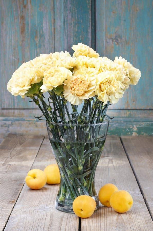 Blumenstrauß von gelben Gartennelken im transparenten Glasvase lizenzfreie stockfotos