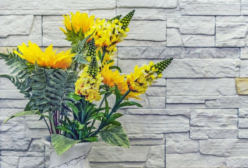 Blumenstrauß von gelben künstlichen Blumen auf einem Steinwandhintergrund stockfotos