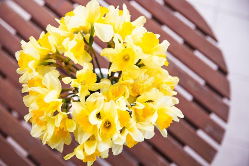 Blumenstrauß von gelben Narzissen in einem weißen Vase auf einem Holztisch im Freien lizenzfreie stockfotos