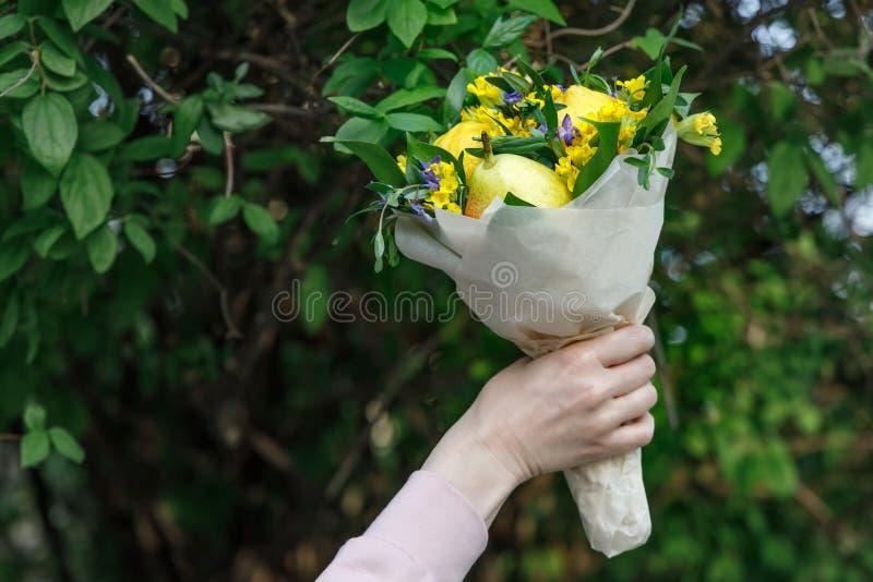 Blumenstrauß von gelben und blauen Blumen und von Früchten in der Hand einer jungen Frau auf einem Hintergrund des grünen Laubs stockbild