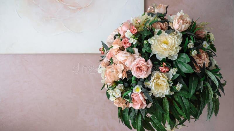 Blumenstrauß von gelben und rosa Blumen vor dem hintergrund der rosa Wand stockfotos