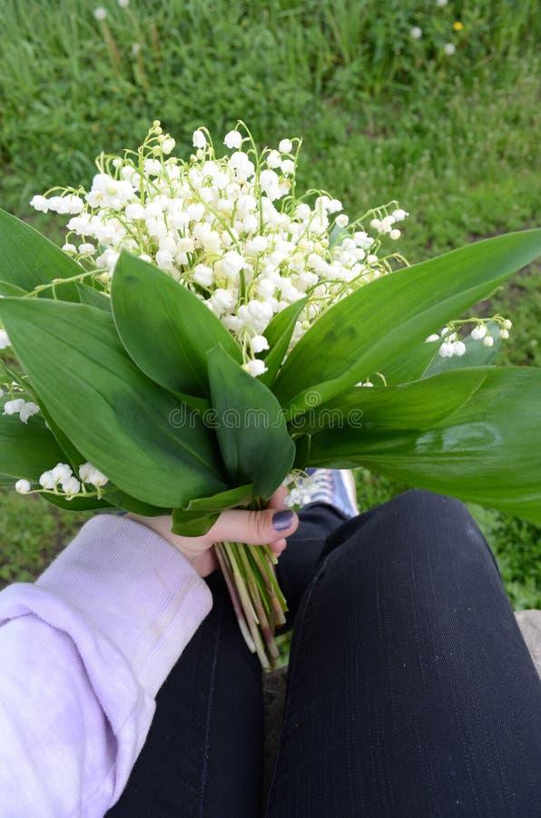 Blumenstrauß von Lilien in der Hand des Mädchens lizenzfreies stockfoto