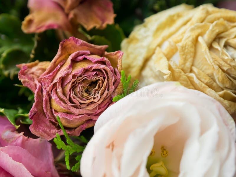Blumenstrauß von Mischblumen auf hölzernem Hintergrund, Rosen, Gartennelke, Eustoma, trockene Blumen stockfotos
