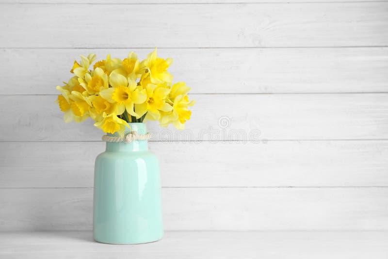 Blumenstrauß von Narzissen im Vase auf Tabelle gegen hölzernen Hintergrund, Raum für Text lizenzfreies stockbild