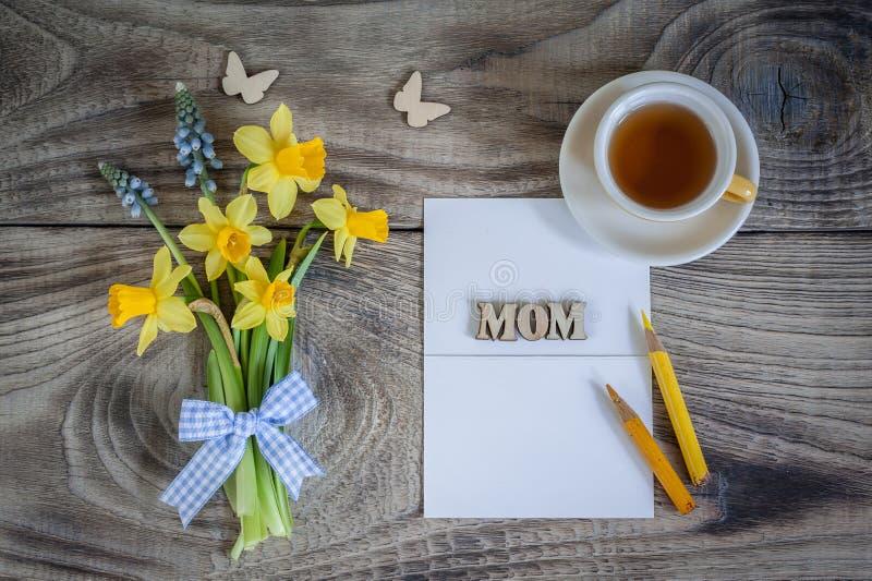 Blumenstrauß von Narzissen und von Muscari auf Holztisch mit Karte, Schmetterlingen und Tasse Tee stockbilder