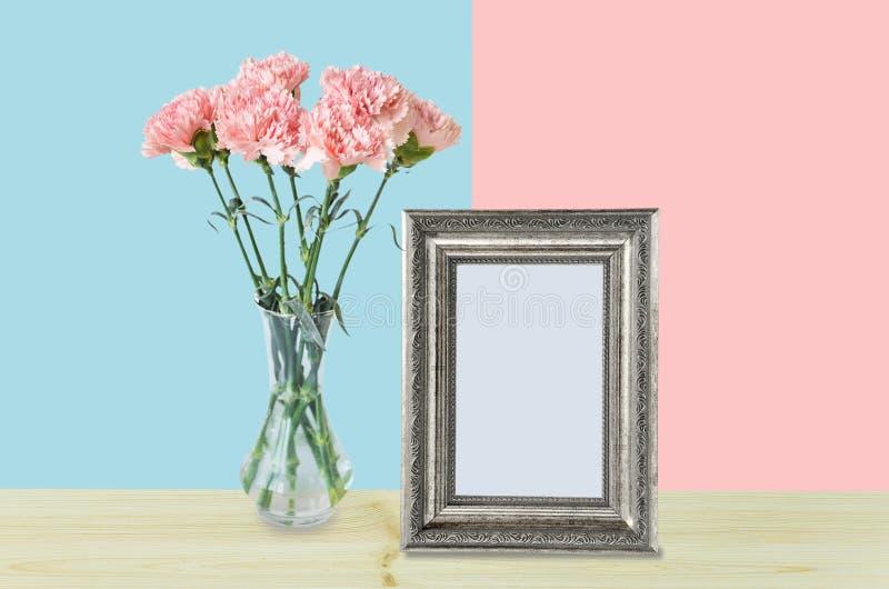 Blumenstrauß von rosa Gartennelkenblumen und von leerem silbernem Fotorahmen lizenzfreies stockfoto