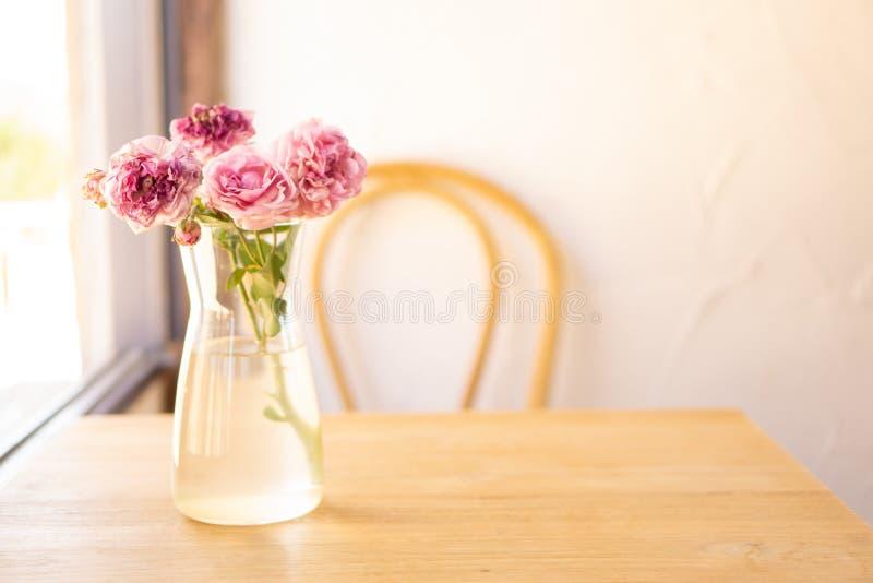 Blumenstrau? von rosa Rosen im Glasvase mit Wasser auf braunem Holztisch, unscharfer Stuhl auf wei?em Hintergrund, Kopienraum lizenzfreie stockbilder