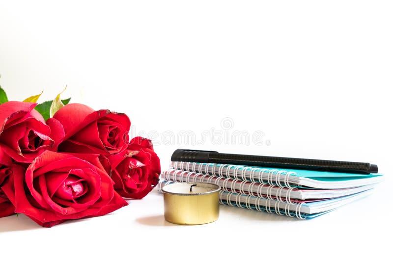 Blumenstrauß von Rosen, von Anmerkungsbüchern, von Stift und von Teelicht auf weißem Hintergrund lizenzfreie stockfotos