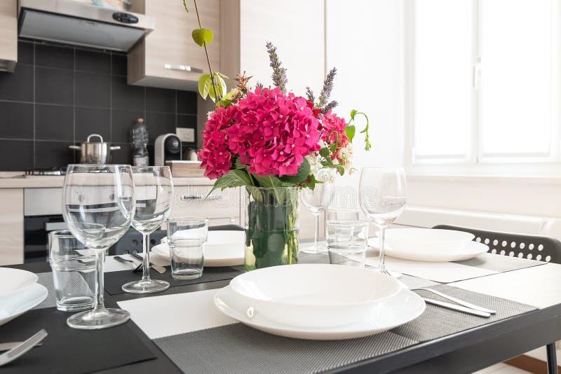 Blumenstrauß von roten Blumen auf Speisetischmenge mit Gläsern und Platten lizenzfreies stockfoto