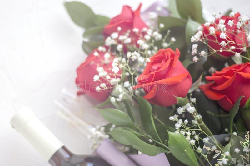 Blumenstrauß von roten Rosen mit einer Flasche Wein auf einem weißen Hintergrund im weißen unscharfen Licht stockbild