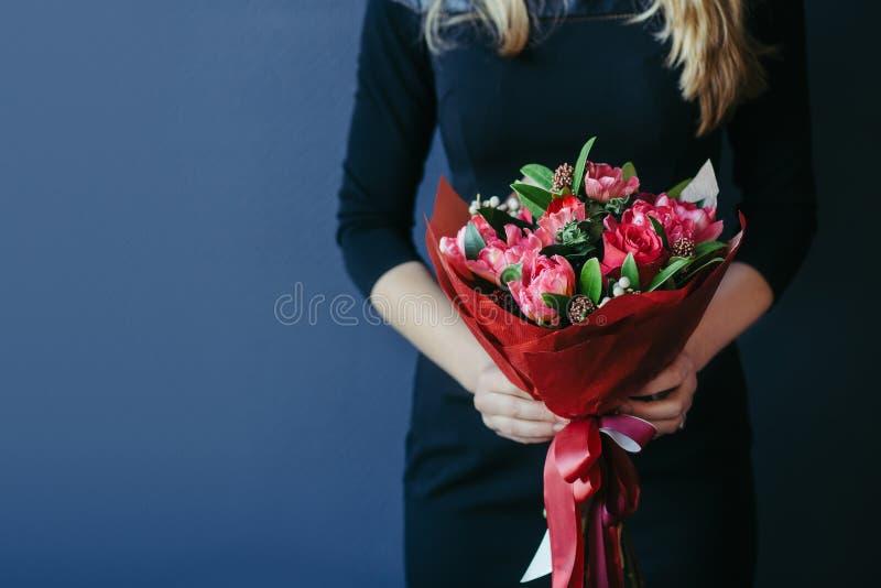 Blumenstrauß von roten Tulpen in girs Händen unrecognisable lizenzfreie stockfotografie