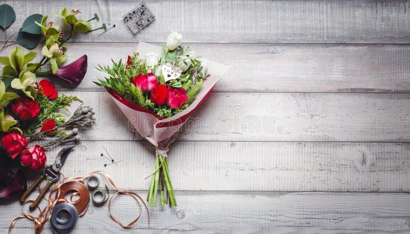 Blumenstrauß von roten und weißen Rosen, von Herzen, von Callas, von Gartennelken und von Bändern auf Tabelle lizenzfreies stockbild