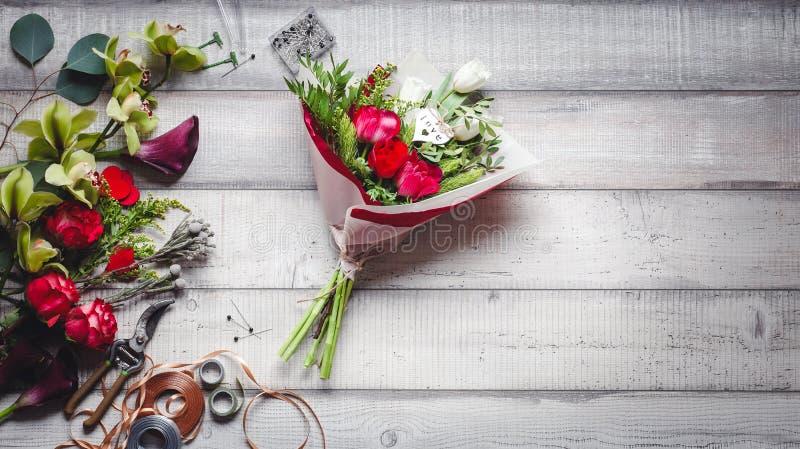Blumenstrauß von roten und weißen Rosen, von Herzen, von Callas, von Gartennelken und von Bändern auf Tabelle lizenzfreie stockfotos
