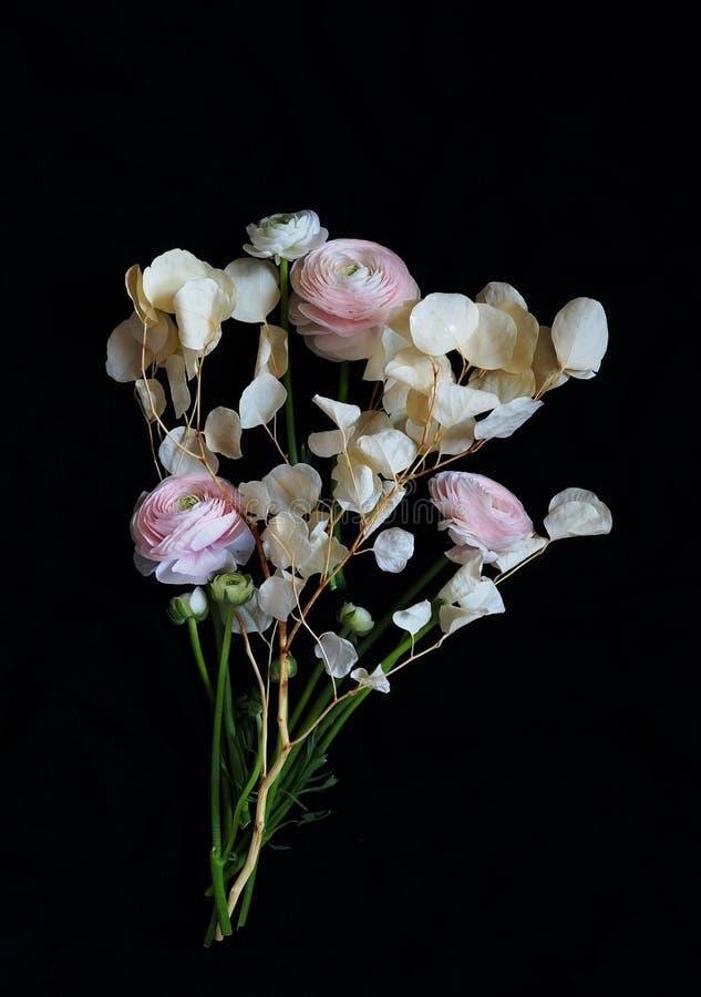 Blumenstrauß von schönem erblassen - rosa Ranunculusblumen und getrocknete Eukalyptusniederlassungen auf einem dunklen Hintergrun lizenzfreie stockbilder