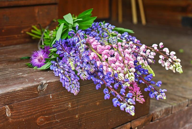 Blumenstrauß von schönen bunten Lupines auf einem hölzernen Hintergrund in einem Landhaus stockfoto