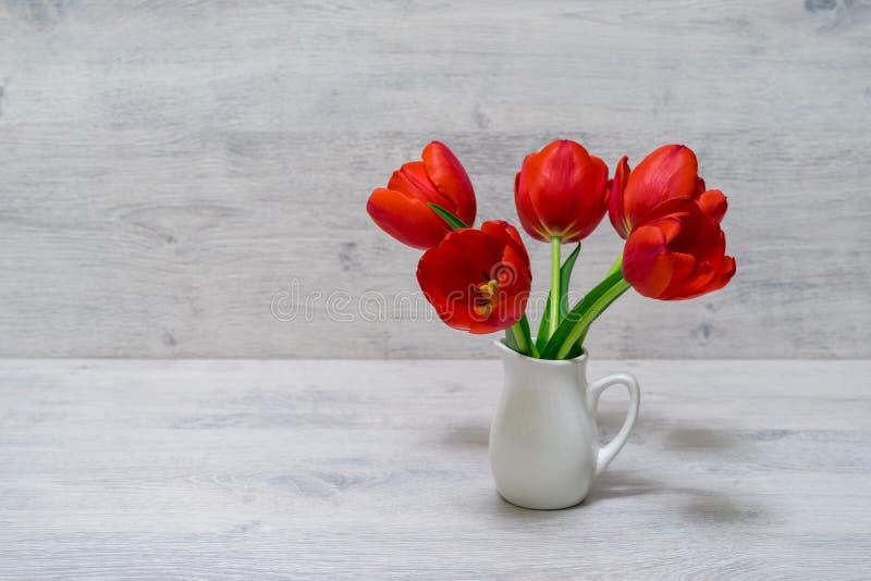 Blumenstrauß von schönen frischen roten Tulpen im kleinen weißen Krug auf hellem hölzernem Hintergrund Valentinsgrußes, Frauen od lizenzfreies stockfoto