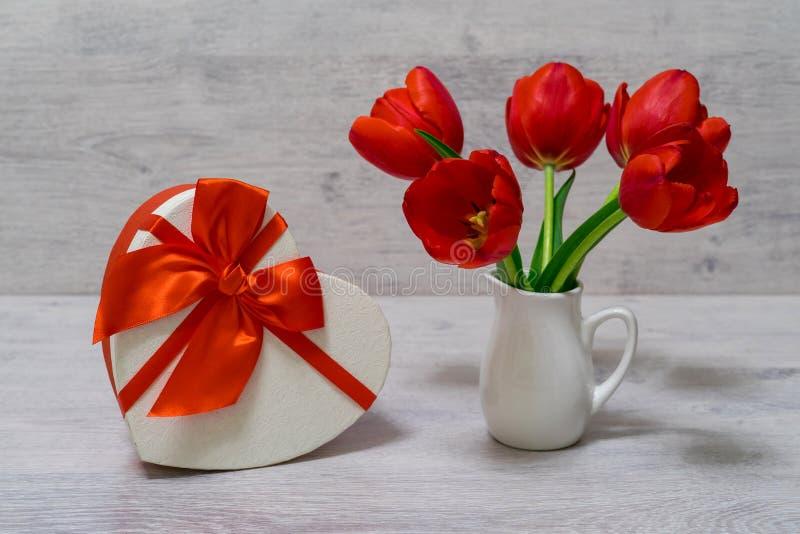 Blumenstrauß von schönen frischen roten Tulpen im kleinen weißen Krug und in der Geschenkbox in der Herzform auf hellem Hintergru stockfoto