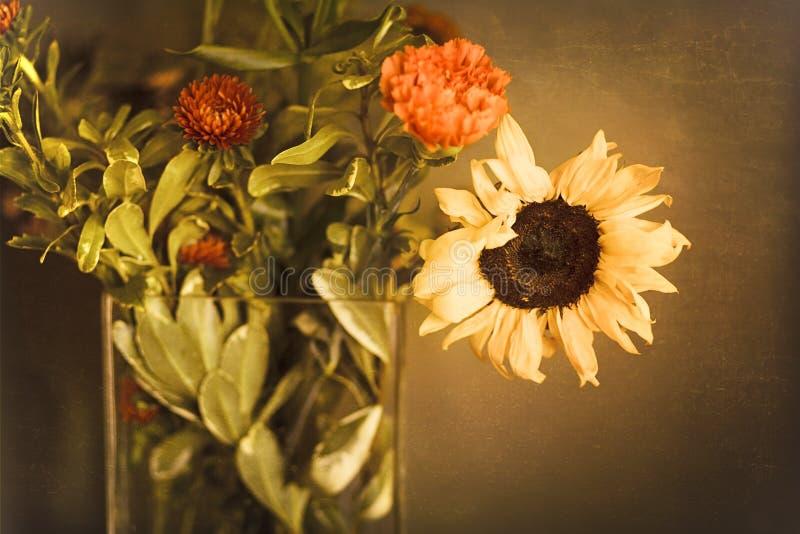 Blumenstrauß von Sonnenblumen und von orange Mamas im Glas- Vase vor strukturierter Gold-Brown-Wand lizenzfreie stockfotos