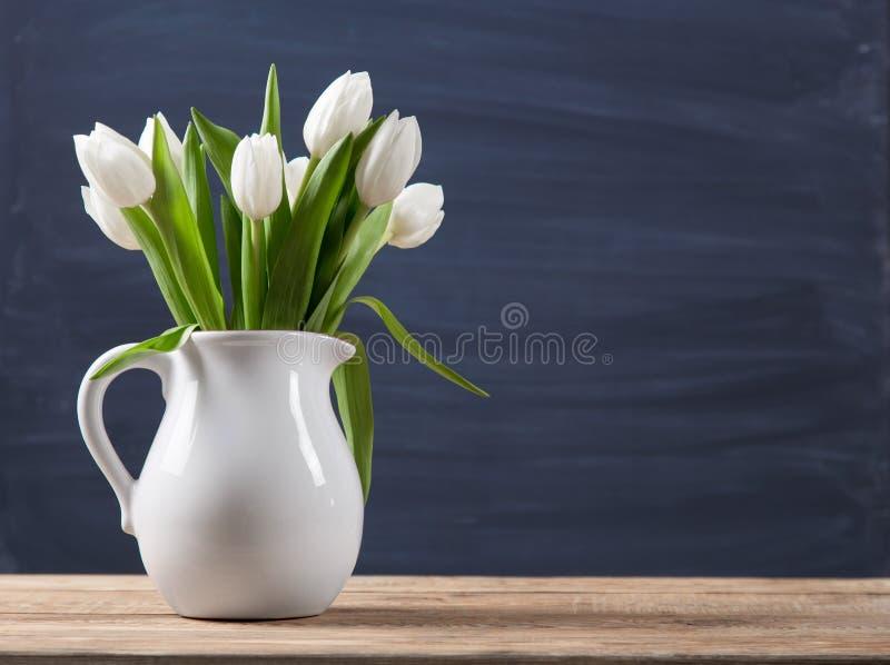 Blumenstrauß von Tulpen in einem altmodischen rustikalen Vasentopf Helle Farbe blüht im weißen Krug auf einem Unschärfehintergrun stockbild
