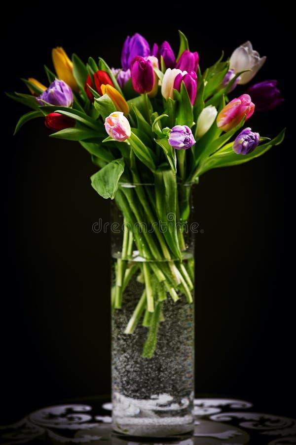 Blumenstrauß von Tulpen im Vase auf Dunkelheit stockfotografie