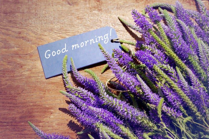Blumenstrauß von violetten wilden Sommerblumen und die blaue Karte mit dem guten Morgen der Aufschrift! stockbilder