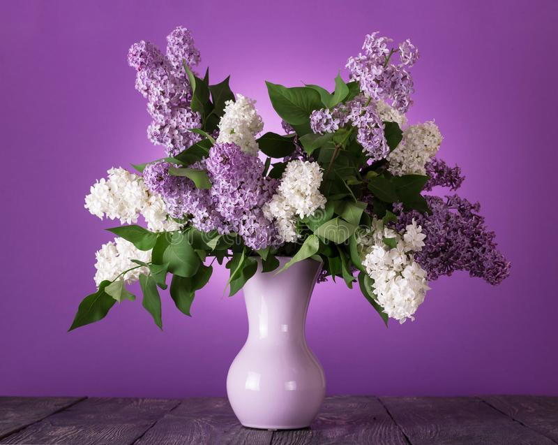 Blumenstrauß von weißen und lila Blumen im Vase auf Tabelle lizenzfreie stockfotos