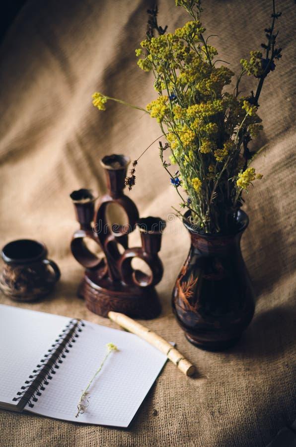 Blumenstrauß von wilden Blumen in einem dunklen Vase lizenzfreie stockfotos