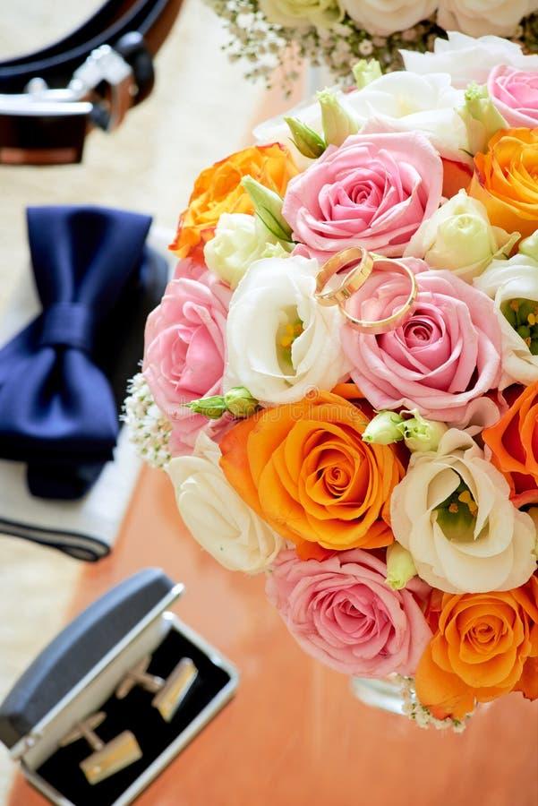 Blumenstraußblumen, Hochzeitsringe und Komponenten stockfoto