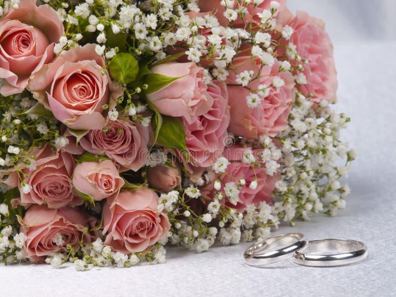 Blumenstraußrosen und Hochzeitsringe lizenzfreies stockbild
