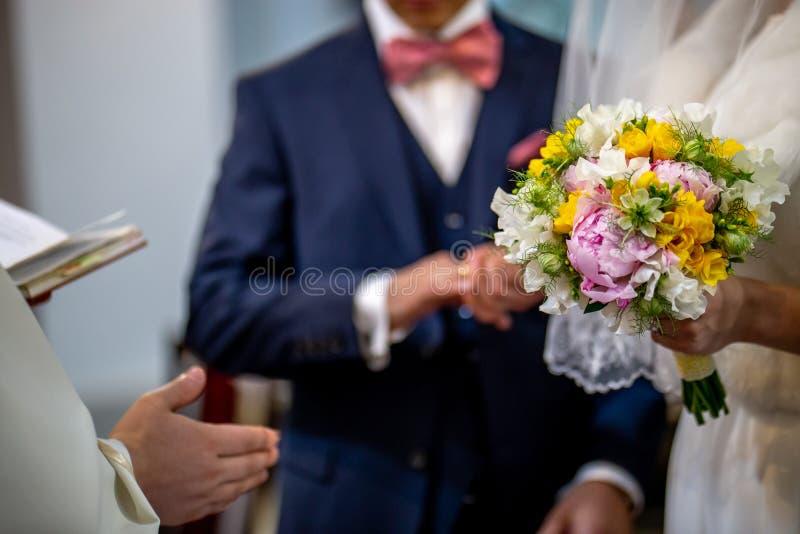 Blumenstrau? von Blumen in der Hand der Braut w?hrend der Trauung stockbild