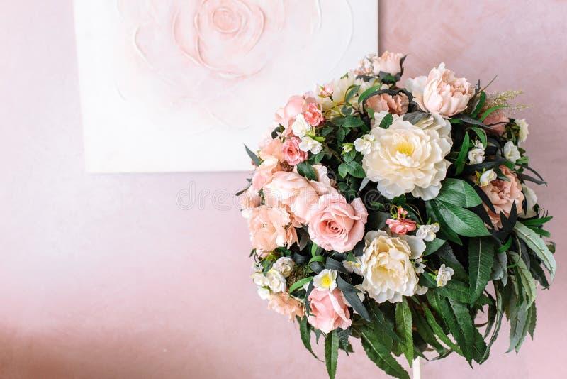 Blumenstrau? von gelben und rosa Blumen vor dem hintergrund des Bildes einer Rose auf einer rosa Wand lizenzfreies stockbild
