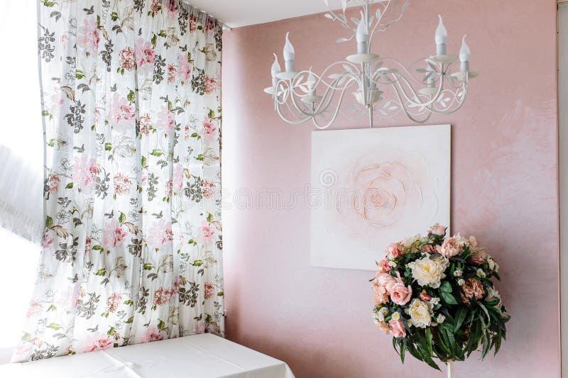 Blumenstrau? von gelben und rosa Blumen vor dem hintergrund des Bildes einer Rose auf einer rosa Wand stockfotografie