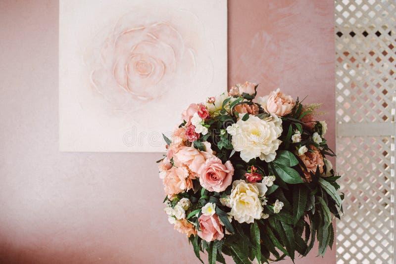 Blumenstrau? von gelben und rosa Blumen vor dem hintergrund einer rosa Wand lizenzfreie stockfotos