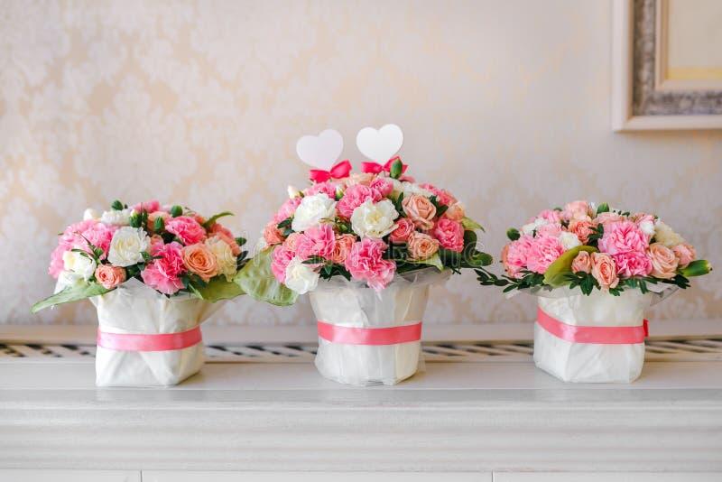 Blumentischschmucke für ein Hochzeitsfest Die Blumensträuße von den rosa und weißen Rosen lizenzfreie stockbilder