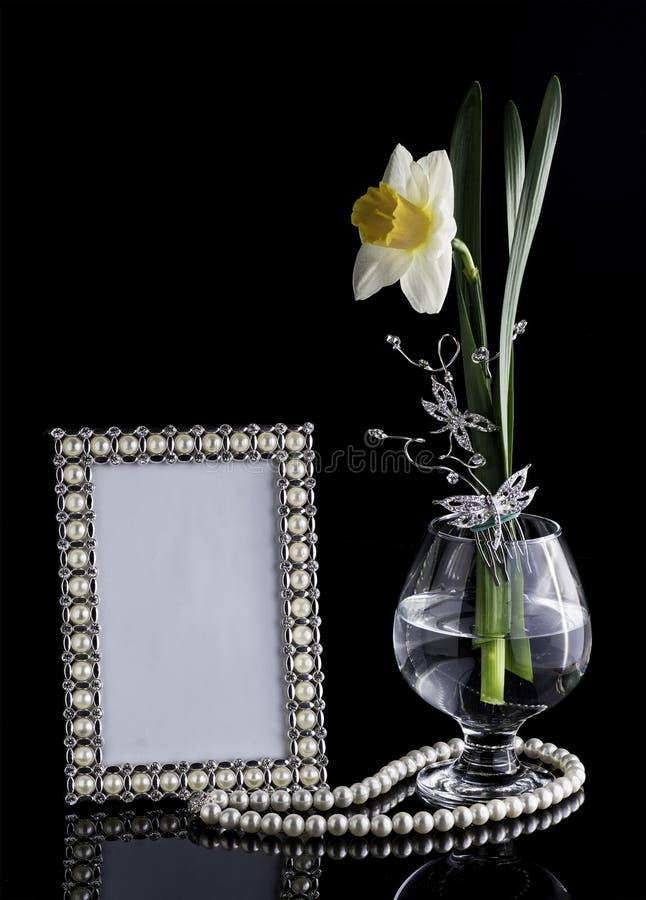 Blumenzusammensetzung mit einem Rahmen und einem Glas stockbild
